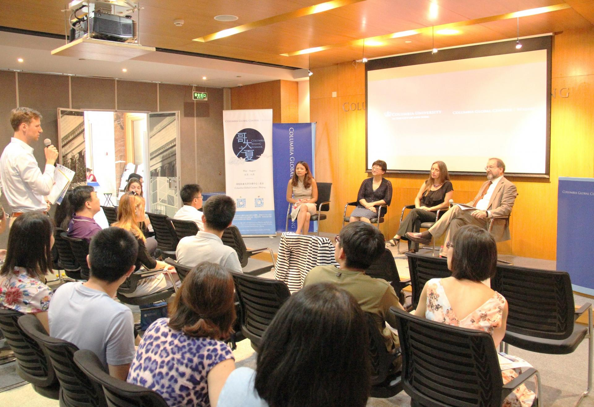 a participant standing asking a question to four panelist during an event at the Beijing Center