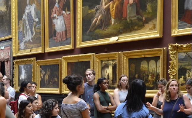 large group of students looking at paintings at a museum