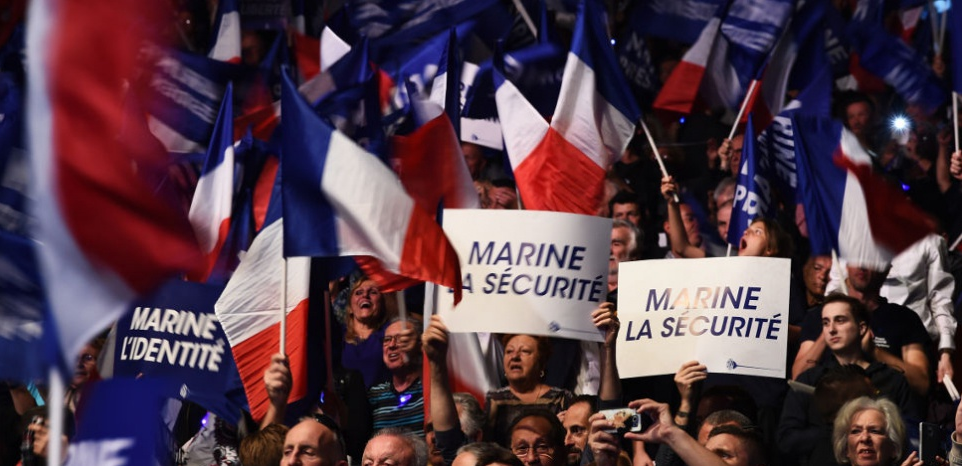 Crowd waving flags at a Marine Le Pen rally on April 19, 2017