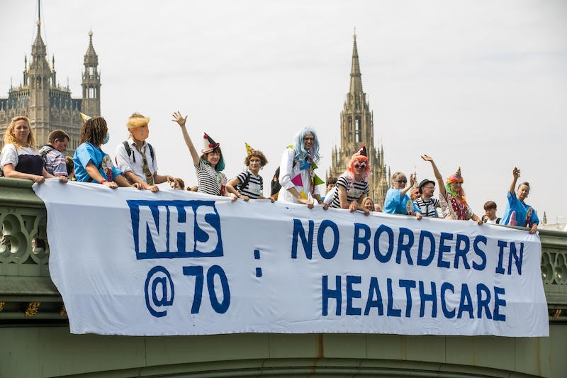 People holding banner on bridge: No Borders in Healthcare
